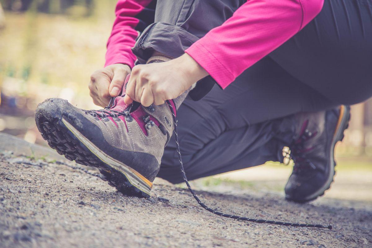 Junge Frau bindet ihre Wanderschuhe, Wanderung