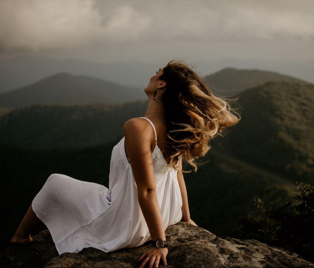 Frau mit weißen Kleid sitzt auf einem Berg, Unplash